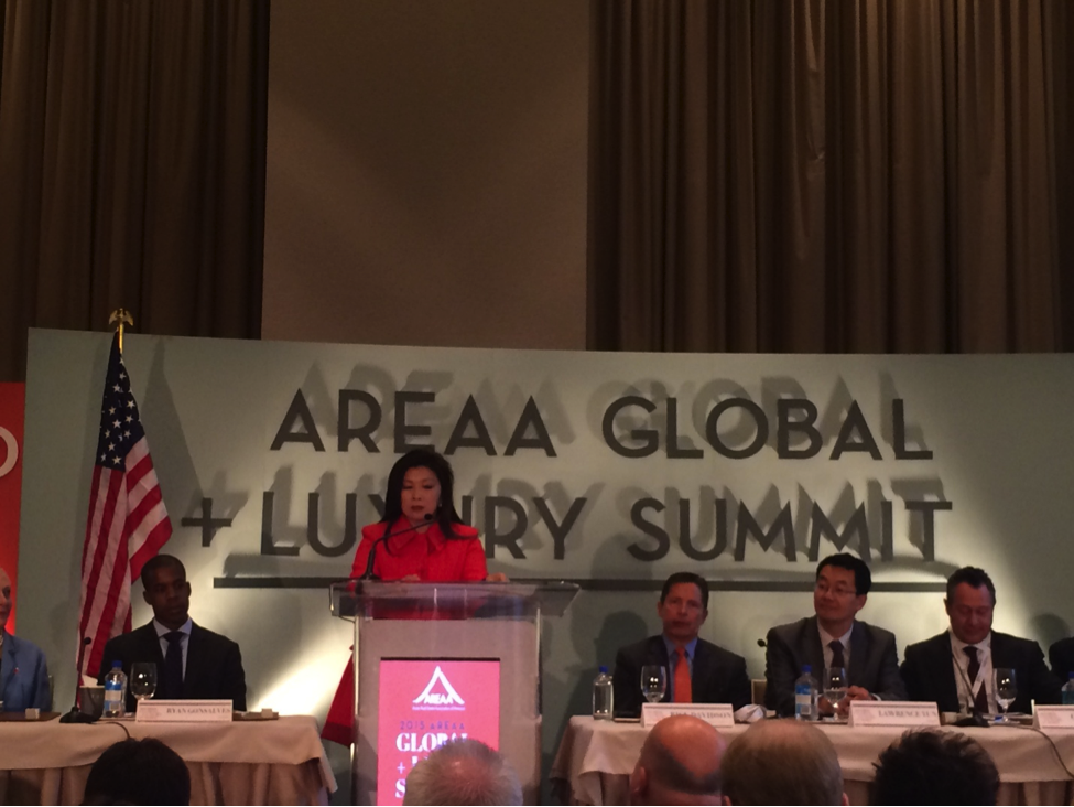 Above and Below: 2015 AREAA Chairwoman moderates a panel of experts on the state of international investment during the Global + Luxury Summit.
