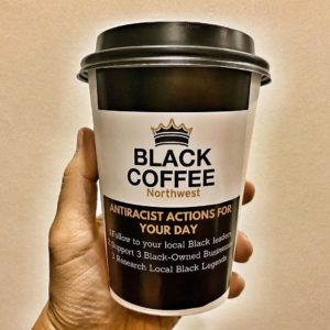 to-go cup of coffee with a label that reads Black Coffee Northwest: Antiracist Actions for Your Day