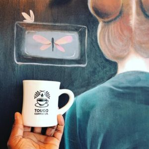 Hand holding up Tougo coffee mug in front of a piece of art that shows the back of a woman's head.